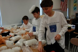 Sixth graders stuff teddy bears in a workshop with the Heavenly Productions Foundation